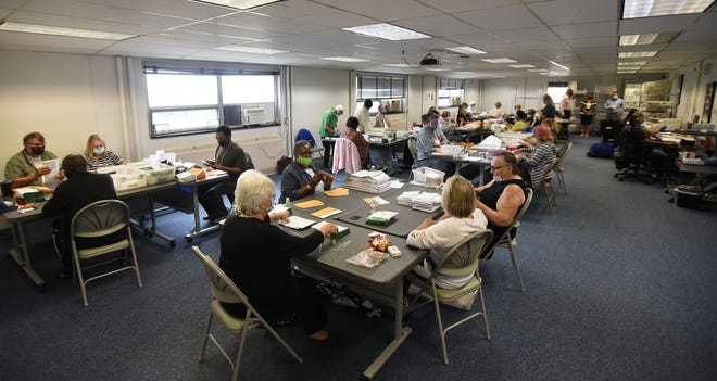Election inspectors work on tallying absentee ballots Tuesday, Aug. 4, 2020, at the Lansing City Clerk's Election Unit office in Lansing.