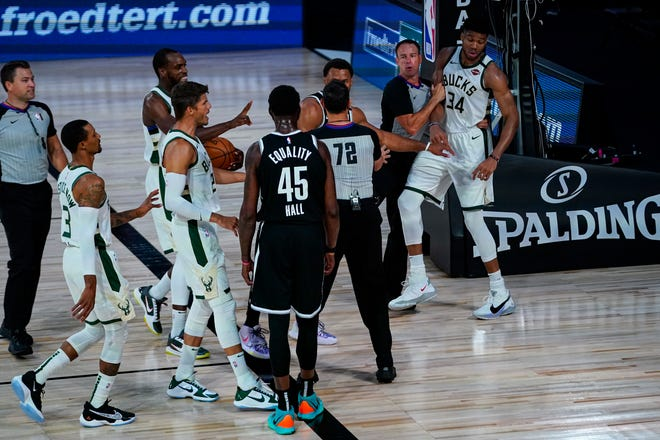 Bucks star Giannis Antetokounmpo is restrained by a referee after Donta Hall (45) of the Nets threw him to the ground during the first half.