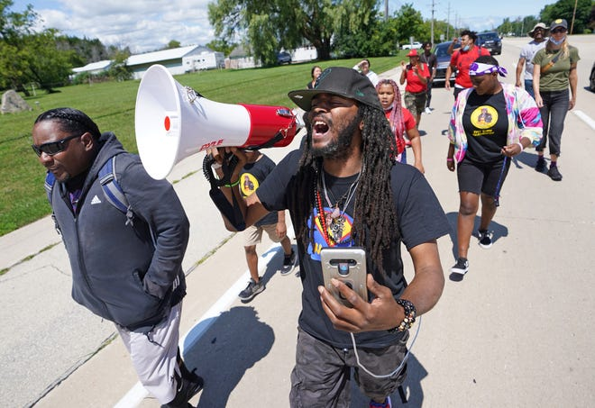 Milwaukee protest leader Frank Sensabaugh, right, who goes by the name Frank Nitty, starts his march to Washington, D.C., along Highway 31 in Caledonia with community activist, Tory Lowe, far left, on Aug. 4.