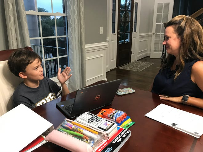 Legacy Middle School student Sam Woodford, 11, explains to his mother, Misty, how his Chromebook programs work after they picked up his laptop on Tuesday. He also gets his school supplies ready on the family dining room table for remote learning beginning Aug. 7.