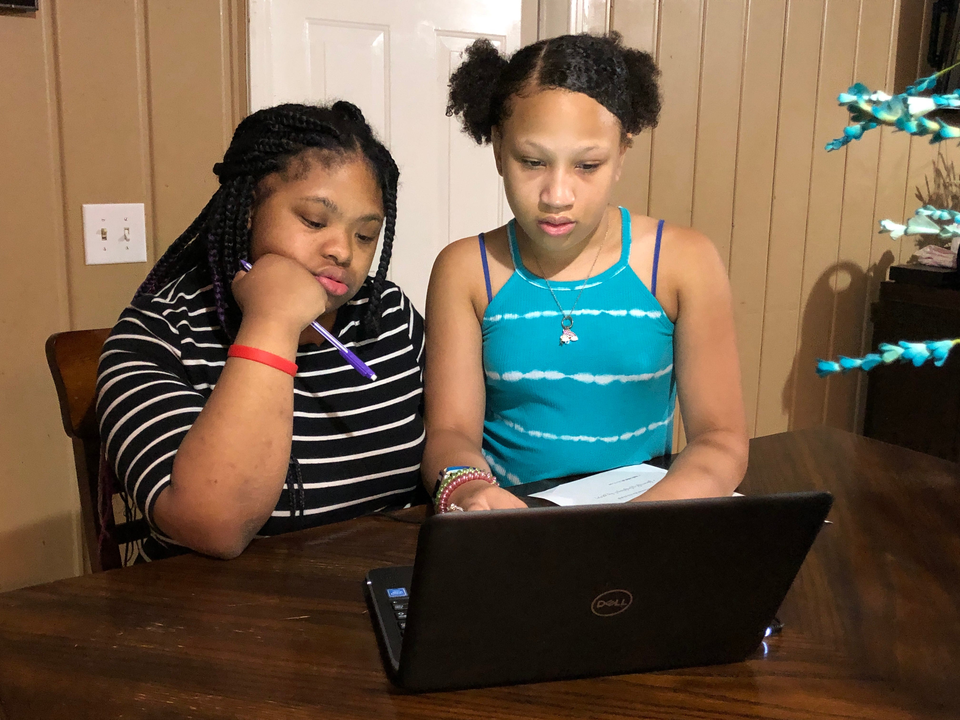 Abigail Alexander, right, a fifth grader at Head Middle Magnet School, helps her sister, Anaya, an exceptional education student at Maplewood High School, try to sign in online for the first day of virtual learning for Metro Nashville Public Schools on Aug. 4.