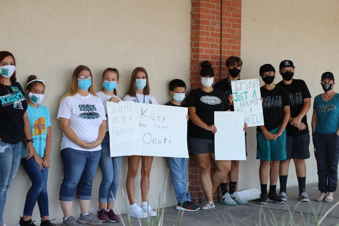 """Near the end of the protest, the group gathers in front of the Las Cruces Public School administration building to pose with their signs in-hand that read """"Students are not a political football,"""" """"Keep the name Oñate,"""" and """"It's not just a name, it's a family"""" on Aug. 4, 2020."""