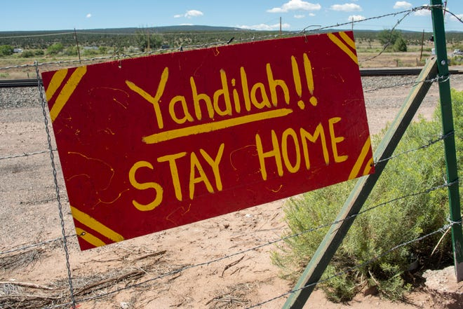 A sign on the road cautions residents to stay home due to the COVID-19 pandemic.