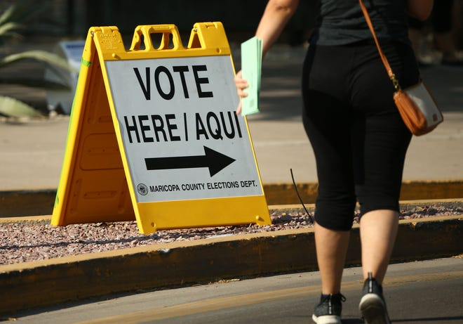 A voter drops off mail-in ballots during the 2020 Arizona Primary election on Aug. 4, 2020, at the Burton Barr Central Library in Phoenix.