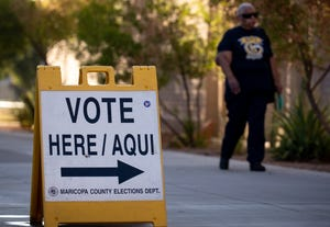 A voter arrives to drop off her ballot, Aug. 4, 2020, at the Mesa Community College polling place.