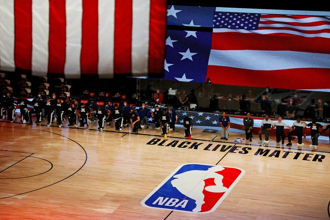 Aug 4, 2020; Lake Buena Vista, USA; Members of the LA Clippers kneel for the national anthem before their game against the Phoenix Suns at The Arena at ESPN Wide World Of Sports Complex on August 04, 2020 in Lake Buena Vista, Florida. Mandatory Credit: Kevin C. Cox/Pool Photo via USA TODAY Sports