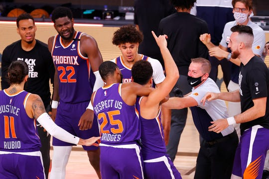 Aug 4, 2020; Lake Buena Vista, USA; Devin Booker #1 of the Phoenix Suns celebrates with teammates after scoring the game winning basket against the LA Clippers at The Arena at ESPN Wide World Of Sports Complex on August 04, 2020 in Lake Buena Vista, Florida. Mandatory Credit: Kevin C. Cox/Pool Photo via USA TODAY Sports