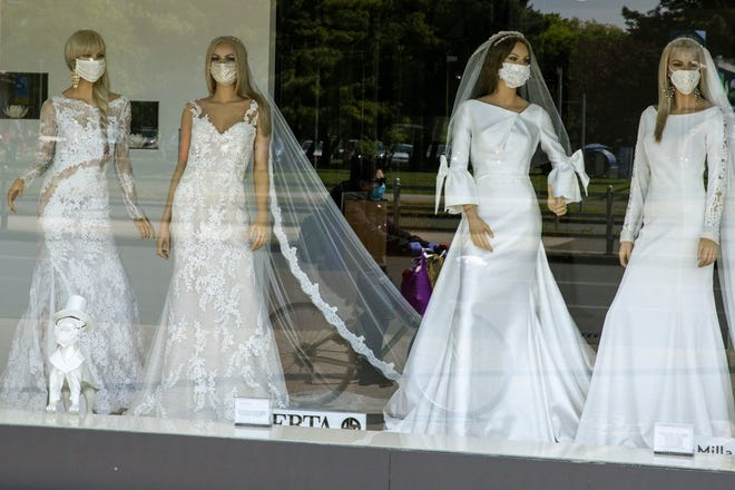 A masked cyclist is reflected in the window of a wedding dress store with mannequins wearing face masks, in Zagreb, Croatia on April 23, 2020. Now that weddings have slowly cranked up under a patchwork of ever-shifting restrictions, horror stories from vendors are rolling in. Many are desperate to work after the coronavirus put an abrupt end to their incomes and feel compelled to put on their masks, grab their cameras and hope for the best. (AP Photo/Darko Bandi)