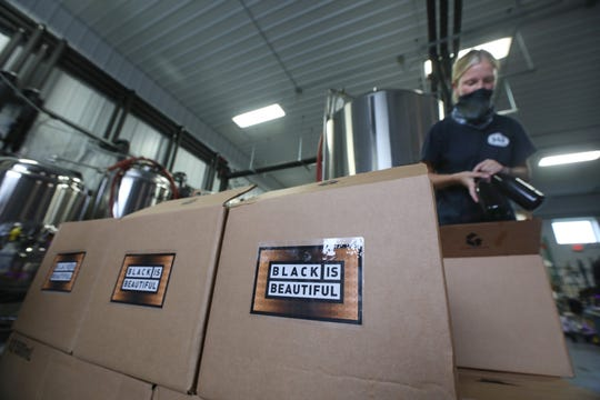 Haley Balcomb fills cases with 1,300 bottles of Black Is Beautiful Imperial Stout as the beer is bottled at Mortalis Brewing Company in Avon, NY, Tuesday, Aug. 4, 2020.