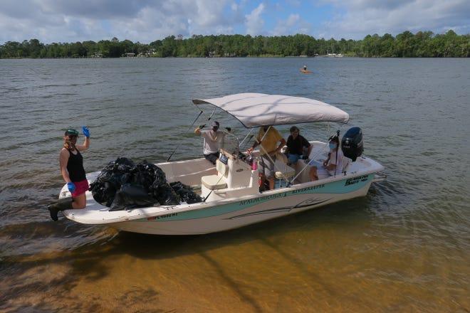 Apalachicola Riverkeeper boat hauling trash bags from large sandbar near Apalachicola.