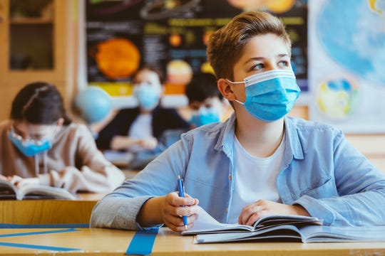 A high school student at school wearing a N95 Face masks.
