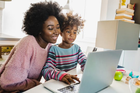 A mother helps her daughter with online school work.