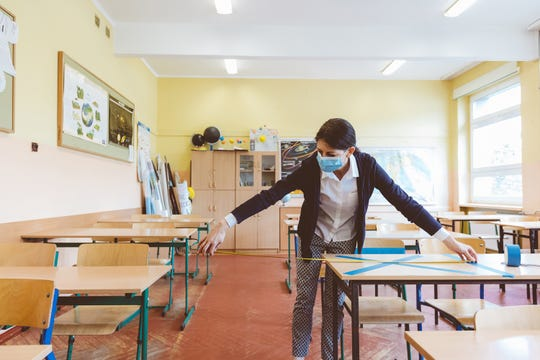 A teacher measures the distance between seats in her classroom.