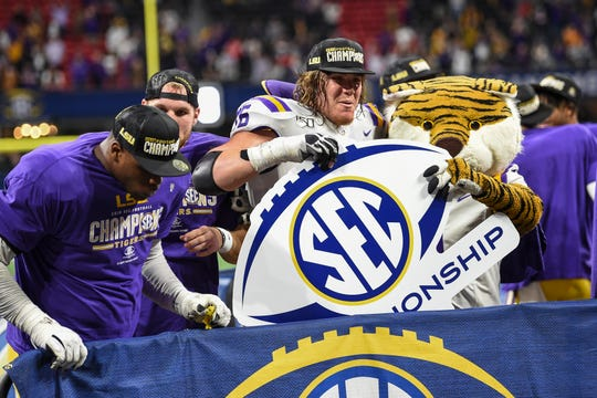 The LSU Tigers celebrate after beating the Georgia Bulldogs in the SEC championship game.