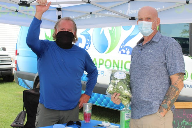 Customer Chuck Ware (right) visits Doug Wood of 302 Aquaponics at the Capital City Farmers Market in Dover.