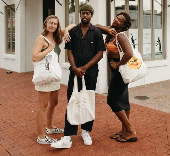 Brianna Kilcullen, Malcolm Jackson and Gigi Lucas pose with limited-edition tote bags developed by Anact with the help of SurfearNEGRA made from hemp and organic cotton. The trio are trying to get more African Americans into the water and surfing. [Stephanie Keeler Photography]