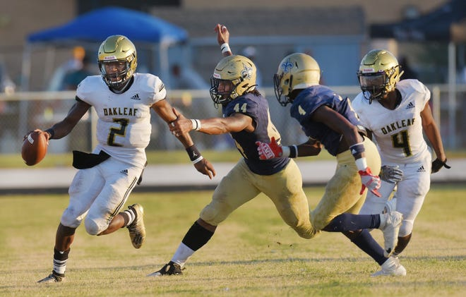 Two Times-Union Super 11 stars in action: Oakleaf quarterback Walter Simmons III (2) attempts to scramble away from Sandalwood linebacker Branden Jennings (44) during a 2019 game.