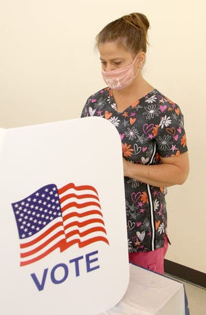 A Kansas voter uses a voting machine to cast her ballot for the 2020 primary election on Tuesday.