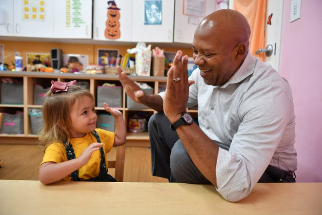 Gene Jones, new CEO of the SKY Family YMCA, gets high-fives from Paisley O'Brien, 2, during a visit to the preschool on Center Road campus in Venice last October. [HERALD-TRIBUNE ARCHIVE PHOTO / MIKE LANG]