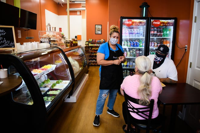 Carmen Alicea takes an order at The Downtown Deli on Hay Street on Wednesday.