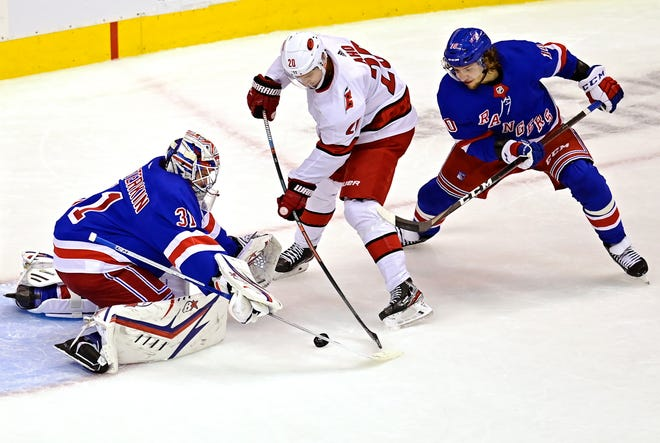 Rangers' goaltender Igor Shesterkin stops Carolina Hurricanes' Sebastian Aho as Rangers' Artemi Panarin defends during the second period of Game 3 in the Eastern Conference qualifying round in Toronto. The rookie Shesterkin made 27 saves in the Rangers' 4-1 loss on Tuesday night. Carolina won the series 3-0. Frank Gunn/The Canadian Press via AP