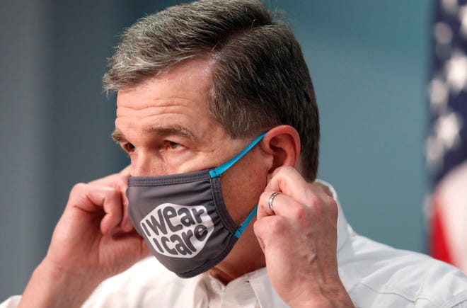Gov. Roy Cooper prepares to take off his mask to talk during a briefing at the Emergency Operations Center in Raleigh, N.C., Wednesday, August 5, 2020.