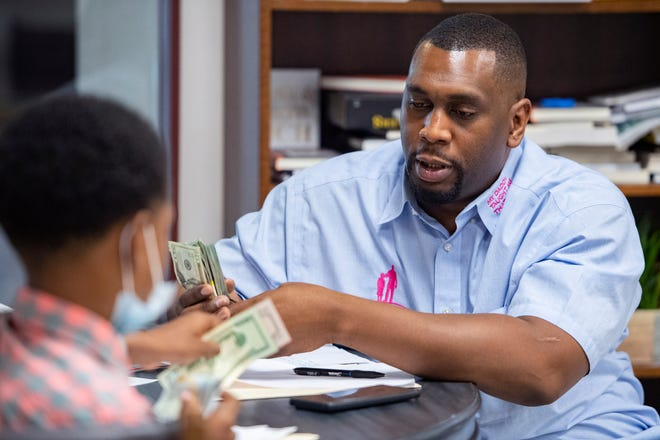 Keynon Lake, founder of My Daddy Taught Me That, pays Kaydan Whiteside, 11, for the hours he spent participating in the past two week's of the organization's tutoring program on July 31, 2020.
