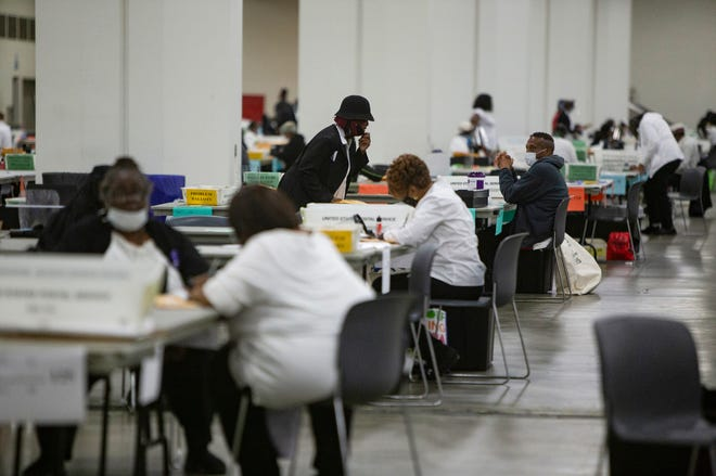 Detroit election workers count absentee ballots cast in the primary elections on Aug. 4, 2020, at the TCF Center in Detroit.