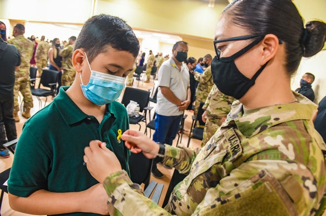 Spc. Ashley Carbullido pins a yellow ribbon pin on her son, Anthony Quenga, during a mobilization ceremony for her and 72 fellow soldiers with the Guam National Guard's Task Force Guåtdia Security Force III at the Guard's Readiness Complex in Barrigada on Wednesday, Aug. 5, 2020. The group will be replacing fellow Guard members coming off a deployment of provided security for the Terminal High Altitude Area Defense anti-ballistic missile defense system installed at the Northwest Field of Andersen Air Force Base in Yigo.