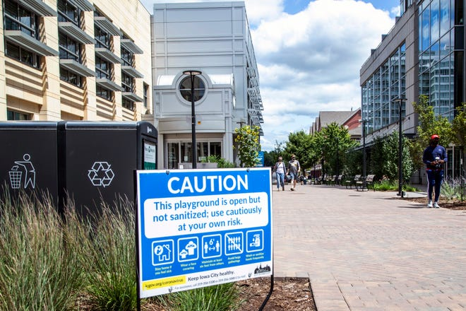 People wearing face masks walk along the Pedestrian Mall past a sign from the City of Iowa City warns that playground equipment has not been sanitized during the novel coronavirus, Monday, Aug. 3, 2020, in Iowa City, Iowa.
