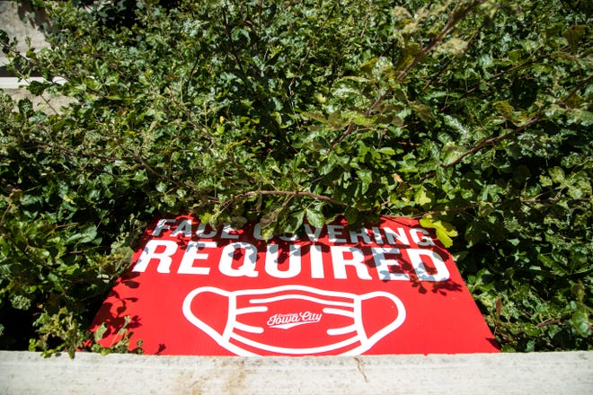 """A sign reading """"face covering required"""" is knocked over in a planter amid the novel coronavirus, Monday, Aug. 3, 2020, in Iowa City, Iowa."""