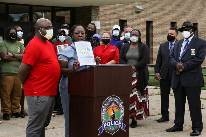 Miranda Burton-Hinton, middle, of Lansing, speaks at a press conference in August 2020 about her son and stepson, who were fatally shot several days earlier.