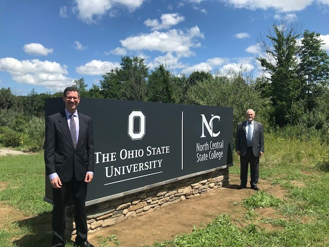 Chamber officials celebrated with Norman Jones, left, dean and director of The Ohio State University Mansfield, and Dorey Diab, president of North Central State College, regarding a new campus sign and entrance along Lexington-Springmill Road.