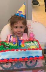 Anne Marie Calligas gets ready to blow out her 5th birthday candle.