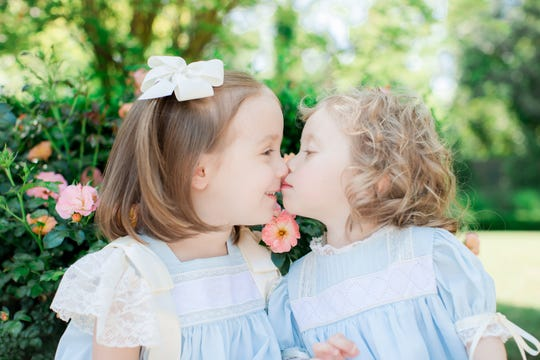 Anne Marie Calligas, right, gives her big sister Isabel Calligas a kiss.