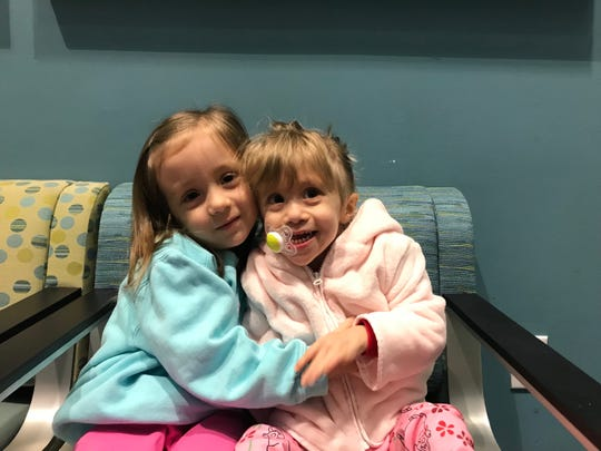 Anne Marie Calligas, right, gets a hug from her big sister Isabel Calligas.