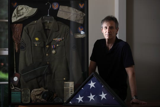Mitchell Bierman poses with WWII mementos his father, Mel Bierman kept from WWII and a flag.  Bierman was one of 27 people the United States sent into the air during the bombing of Hiroshima, which took place 75 years ago this week. Bierman, who was born in 1922, grew up in Passaic and died in 2013. Monday August 3, 2020