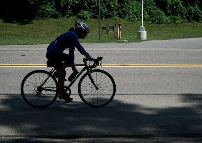 A cyclist pedals along Hines Drive in Westland on Aug. 5, 2020.