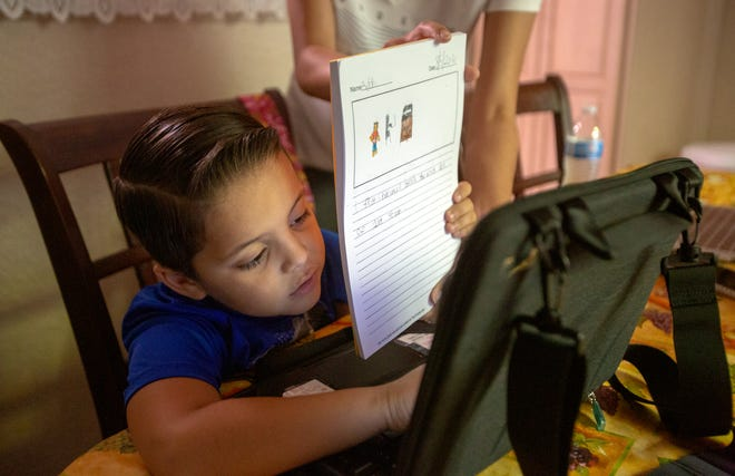 Katherine Finchy Elementary first-grader Adan Ortiz submits his written work on the first day of distance learning at his grandmother's house in Desert Hot Springs, Calif., on Wednesday, August 5, 2020.