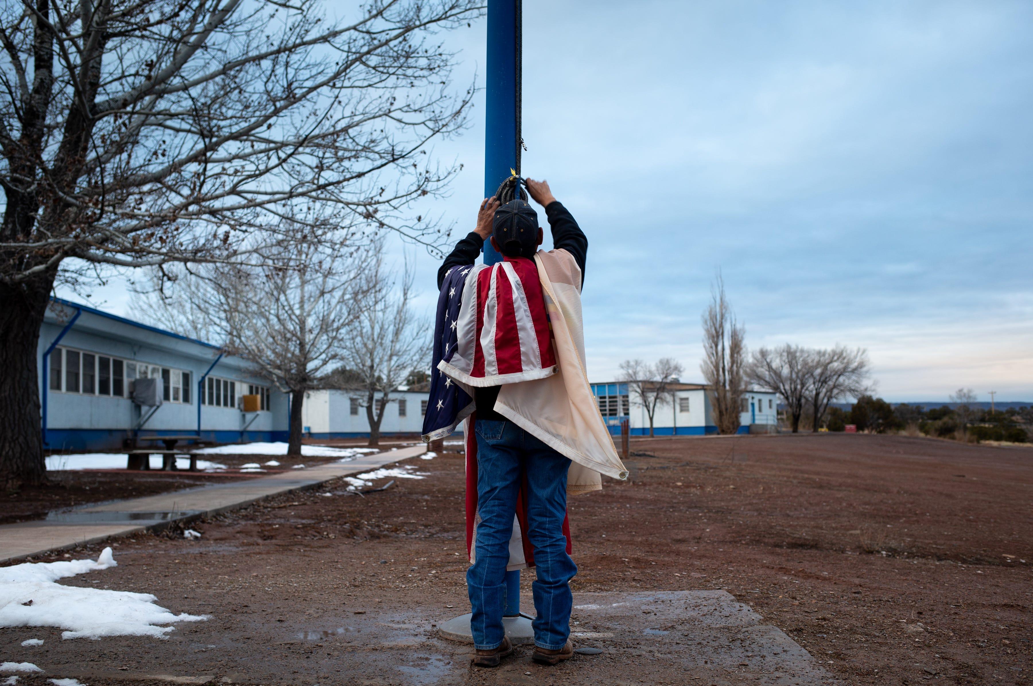 Melvin Peshlaka lowers the U.S. flag and the Navajo Nation flag outside Hunters Point Boarding School.