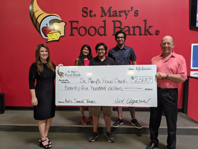 Avi Agarwal, his mother and his brother present a check made out for $2,500 to St. Mary's Food Bank on August 5, 2020.