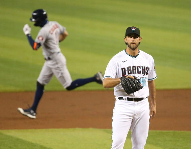Arizona Diamondbacks starting pitcher Madison Bumgarner (40) waits for a new baseball as Houston Astros' Carlos Correa (1) rounds the bases after hitting a solo home run during the second inning at Chase Field August 4, 2020.