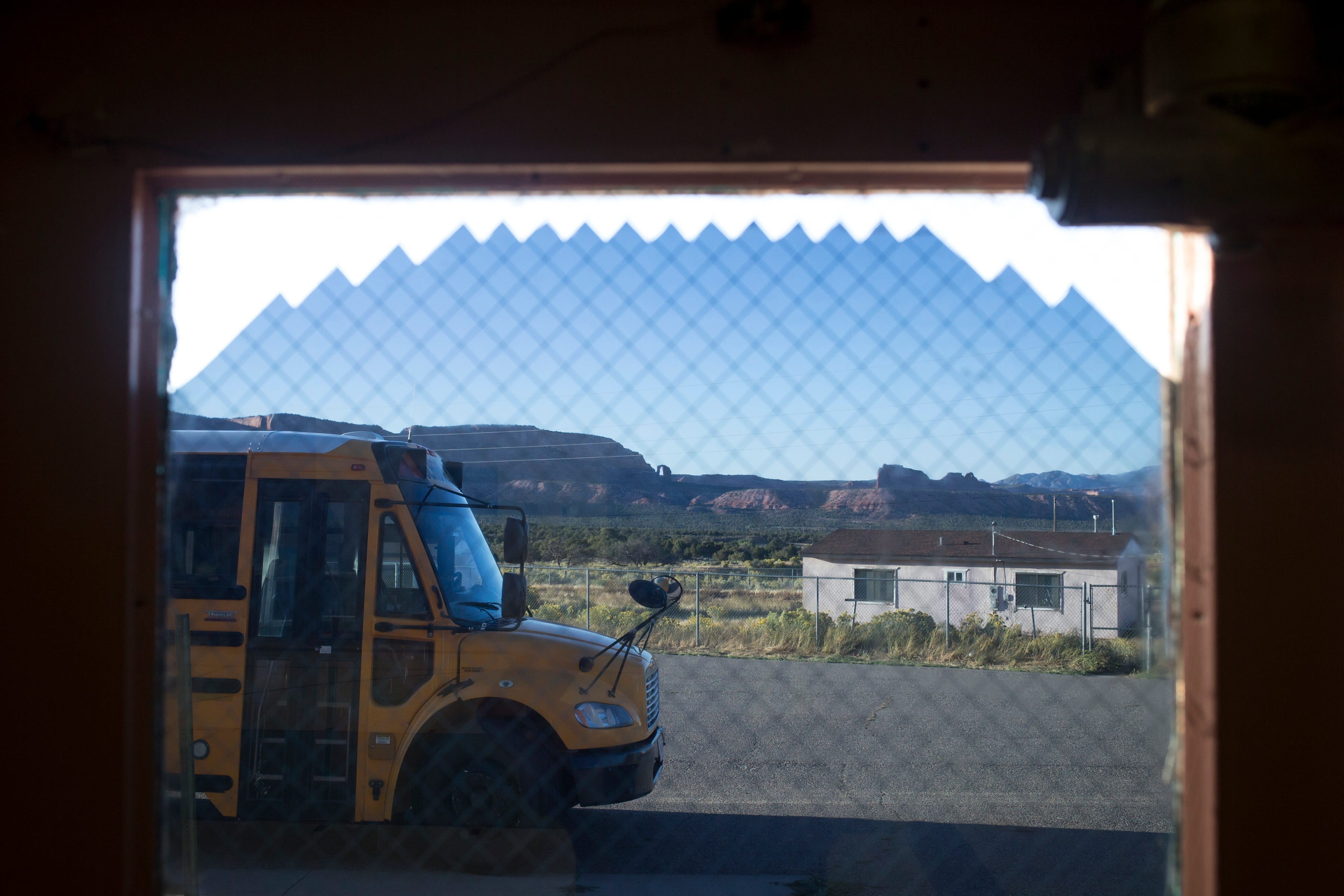A bus and a condemned staff house are shown Oct. 2, 2019, at Cove Day School, a school run by the BIE in Cove, Arizona.