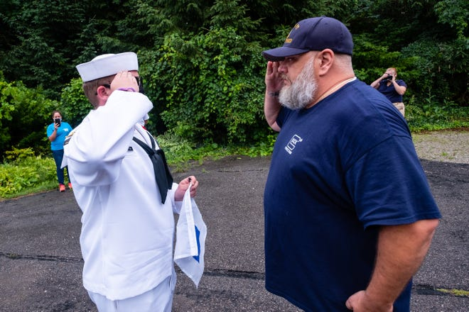 U.S. Naval Sea Cadets Corps F.C. Sherman Division Petty Officer 1st Class Jacob Pemberton, left, and retired U.S. Navy Chief Petty Officer Garrett Powell salute each other Tuesday, Aug. 4, 2020, in Port Huron. The sea cadets presented Powell with a replacement signal flag after his was stolen last month.