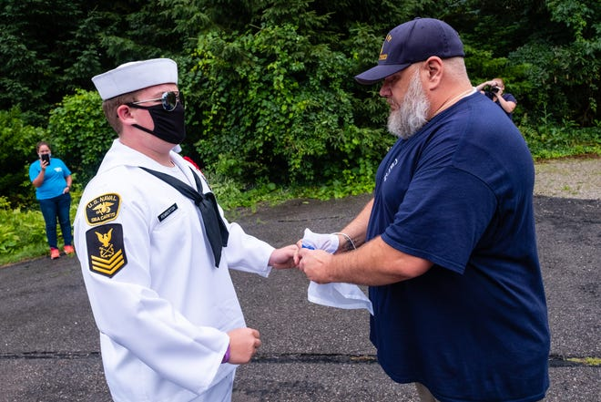 U.S. Naval Sea Cadets Corps F.C. Sherman Division Petty Officer 1st Class Jacob Pemberton, left, presnts retired U.S. Navy Chief Petty Officer Garrett Powell with a signal flag Tuesday, Aug. 4, 2020, in Port Huron. The sea cadets presented Powell with a replacement signal flag after his was stolen.