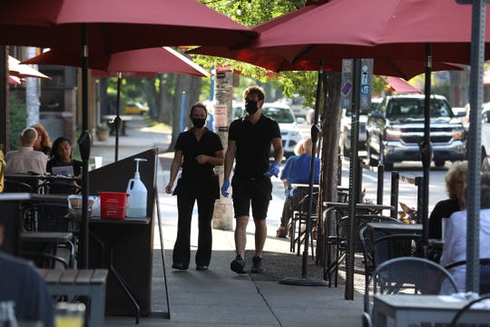 Waitstaff head back inside Jine's Restaurant on Park Ave. in Rochester on August 5, 2020.