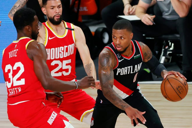 Portland Trail Blazers' Damian Lillard (0) handles the ball against Houston Rockets' Jeff Green (32) and Austin Rivers (25) during the first half of an NBA basketball game Tuesday, Aug. 4, 2020, in Lake Buena Vista, Fla.