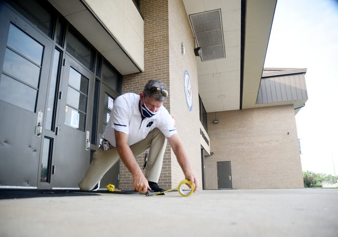 North Desoto High School teacher Bo Odom puts down tape to help with social distancing at the school.