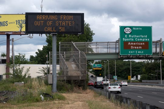 A sign advises out-of-state visitors to call and learn if they should self-quarantine for two weeks in Secaucus, New Jersey, Tuesday, June 30, 2020.