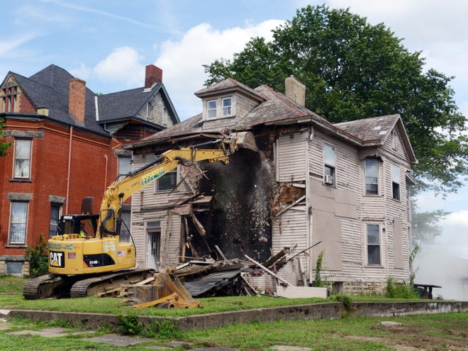 Zemba Brothers demolishes two houses in the 900 block of Maple Avenue on Wednesday in Zanesville. The property, owned by Ryan Dodson, will soon be home to new apartments.